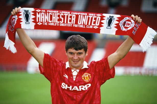New Manchester United signing Roy Keane poses with a club scarf at Old Trafford after signing from Nottingham Forest ahead of the 1993/94 season.