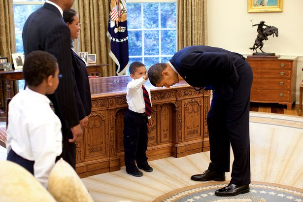 Jacob Philadelphia, 5, center, the son of a White House staff member, touches President Barack Obama's hair to see if it feels like his