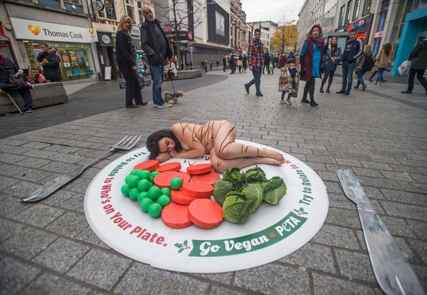 Campaigners from Peta turned heads in Liverpool's Lord Street after stripping nearly naked and lying on a giant plate to encourage shoppers to go vegan this Christmas.