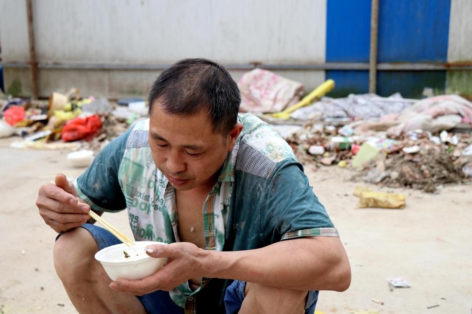 垃圾堆旁吃飯的農民工大哥:掙錢最重要! - 壹讀
