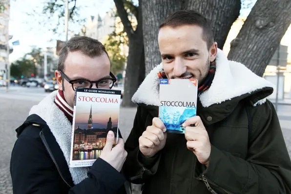 Andrea from Dolce & Gabbana and friend holding Stoccolma guide books