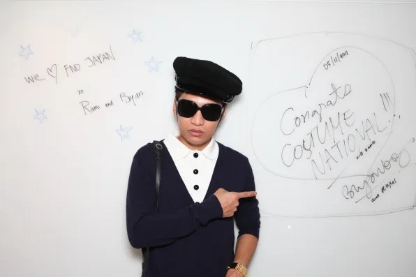 Bryanboy in front of Costume National autograph wall