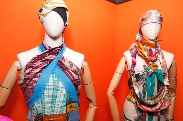 Two mannequins wearing Hermes silk scarves draped as halter tops