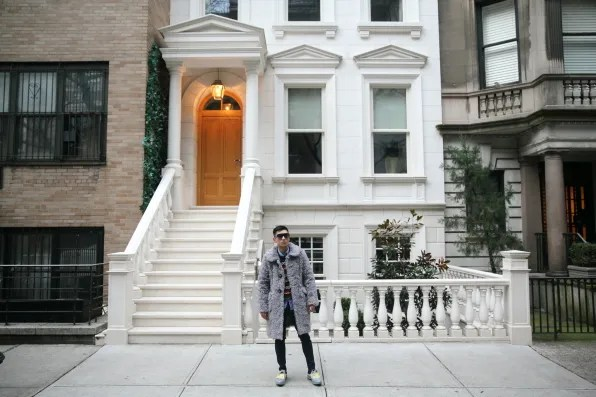 Bryanboy standing outside a white marble townhouse in New York City