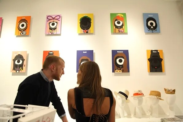 Anna dello Russo looking at portraits by Darcel at Colette