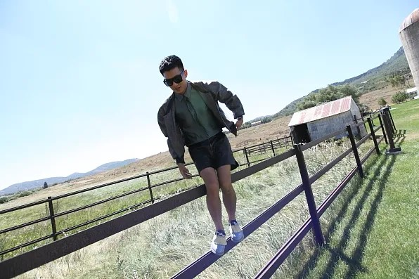 Bryanboy walking on top of a farm fence