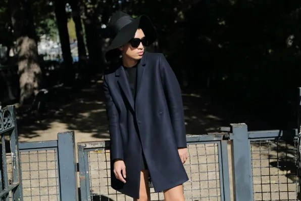 Bryanboy wearing a navy blue COS coat at Canal Saint Martin, Paris