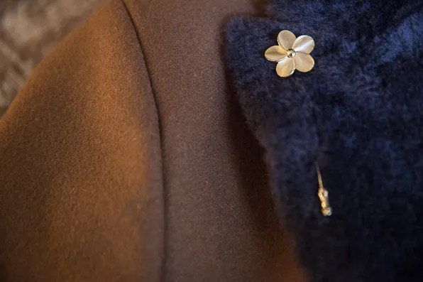 Gold floral pin on Armani jacket