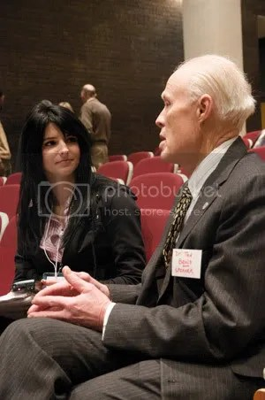 Dr. Ted Beals talks to a journalist during a break in the Symposium.