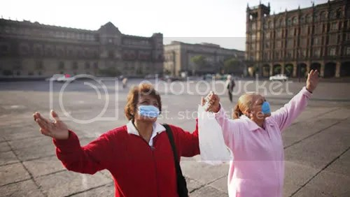 Women wearing surgical masks pray in the Zocalo plaza in Mexico City on Sunday. (Dario Lopez-Mills/Associated Press)