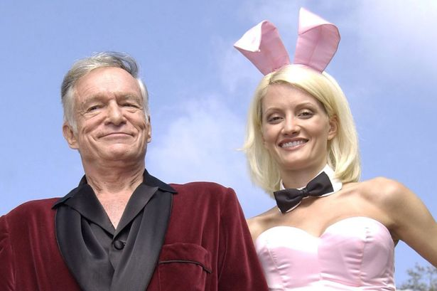 """Playboy founder Hugh Hefner and Playboy bunny Holly Madison perform a scene during the filming of a commercial for """"X Games IX"""" at the Playboy Mansion May 6, 2003 in Holmby Hills, California"""