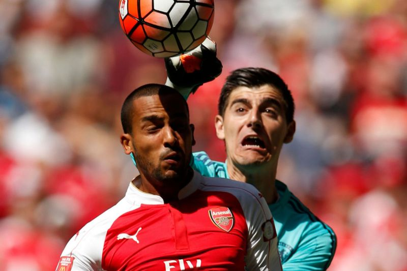 Theo Walcott in action with Thibaut Courtois