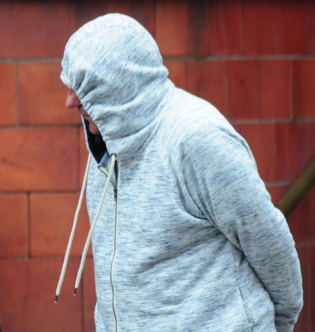 Joynes, 59, hides his face as he is snapped by photographers