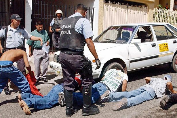Police officers arrest people during an operation against gangs in San Pedro Sula, Honduras, 26 March 2005.