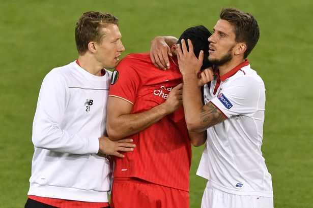 Emre Can is consoled by Daniel Carrico after Sevilla won the UEFA Europa League