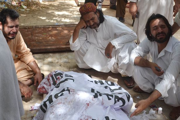 Pakistani relatives mourn beside the body of a blast victim after a bomb explosion at a government hospital premises in Quetta