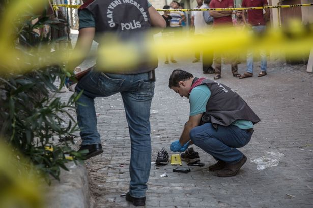 Turkish police work near the explosion scene following a late night attack on a wedding party