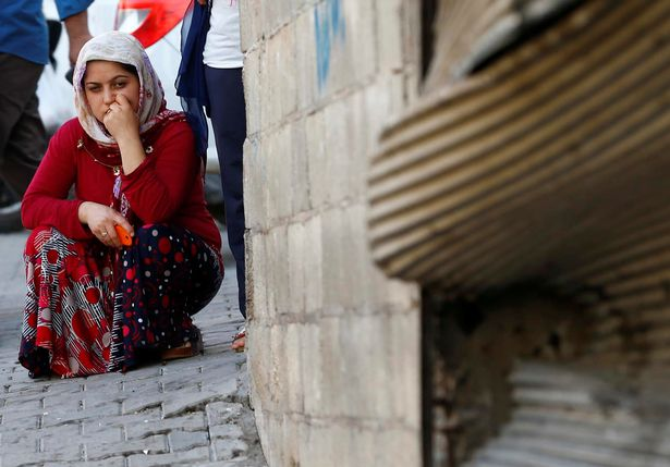 A woman pauses as she sits near the scene of an explosion