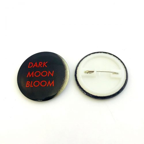 Black button badge with red writing front and back