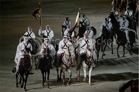 Desert horsemen on Arabian horses enter the Khalifa Stadium