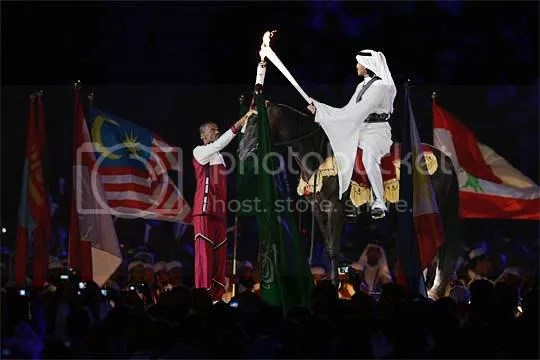 Talal Mansour passes the flame to HE Sheikh Mohammed Bin Hamad Al-Thani on horseback, who had the honour of lighting the cauldron
