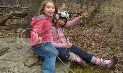 Two girls sit and pose on rock among leaf covered woods arms outstretched (Big Sky Wide).