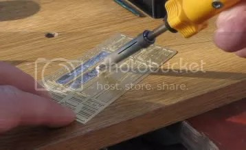 Photo#3: The first job is to tap in the bolt heads. I do this with a pin whilst the brass etch is resting on a piece of hardboard. A light tap is enough. When this is done flux and solder (tin) the insides of both sides and ends. When completed cut the parts out of the fret and clean up the rough edges with a file.