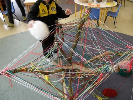 Children weaving a string spider web