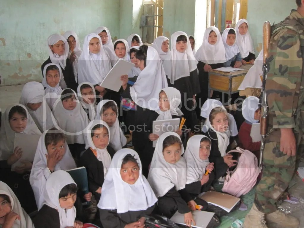 Schoolgirls in Afghanistan, with only one desk between them. Photo courtesy of Rex Temple.