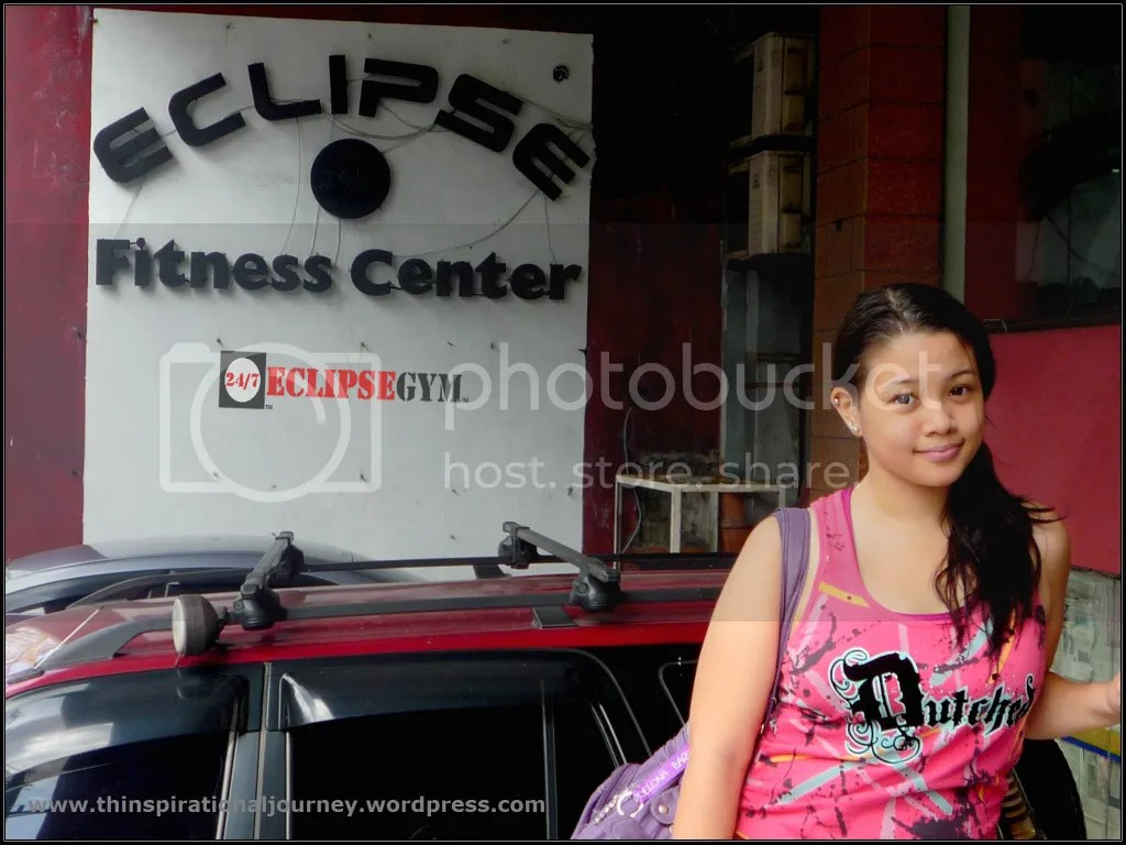 Lara Novales at the Entrance of Eclipse Fitness Center with the old logo.