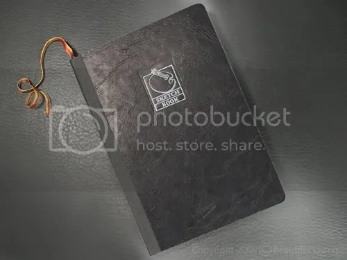 The Exacompta Sketchbook has a textured, black, cardboard cover that begs to be embellished with metallic markers and collage. The logo on the front cover is in a silver foil and measures just over an inch. This would make an excellent art journal or travel journal.