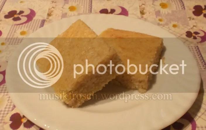 Zwei Stücke goldgelber Blechkuchen auf einem weißen Teller