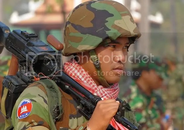 A Cambodian soldier carries a machine gun