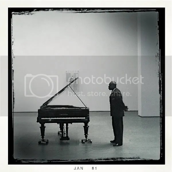 photo of man standing next to piano
