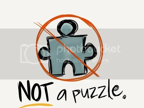 "A puzzle piece meant to resemble the Autism Speaks logo as if hand drawn, with a red ""no"" sign over it. Underneath there are black letters which say ""NOT a puzzle."""