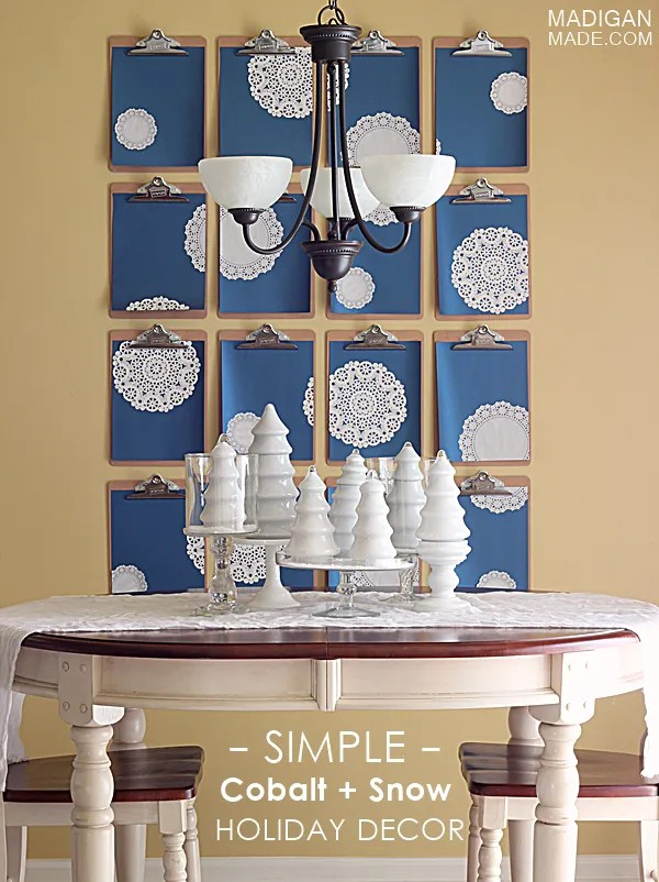 Wintery holiday decor idea: Giant clipboard wall with doily snowflakes and white trees.