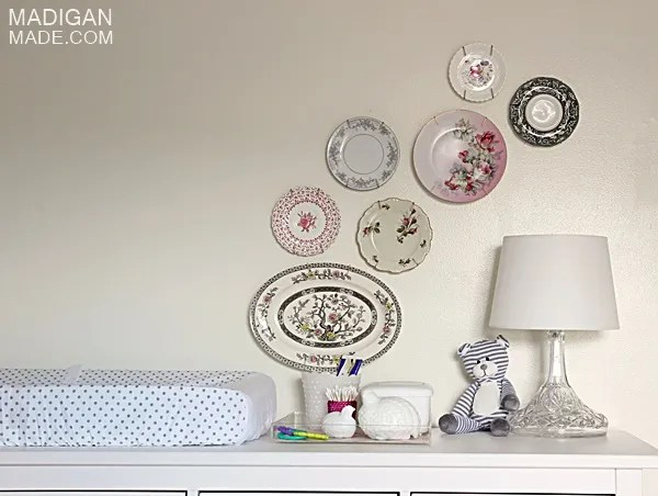 use a dresser as a changing table for a nursery (love the vintage plate wall, too)