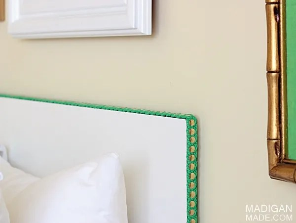 faux nail head trim using brass thumb tacks for a DIY headboard