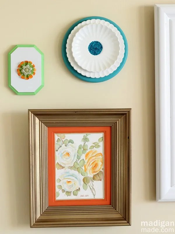 to add a little more interest to the wall i hung up some other objects i found this floral plate from the craft store was the perfect orange color