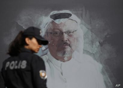 A Turkish police officer walks past a picture of slain Saudi journalist Jamal Khashoggi prior to a ceremony, near the Saudi…