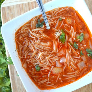 Overheard shot of Mexican Sopa highlighting the noodles and onion in the broth