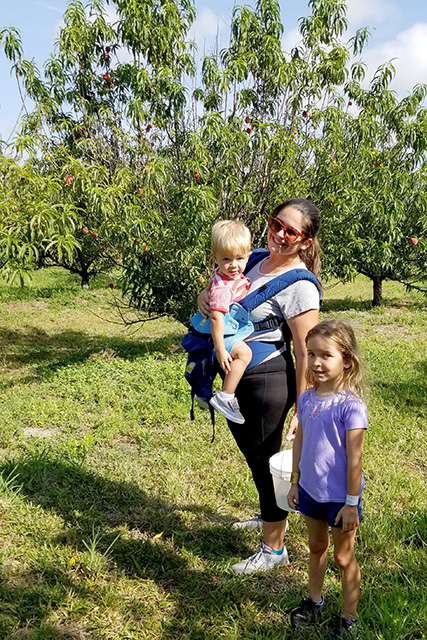 Mother and children at a peach picking farm