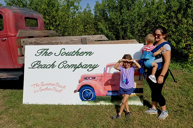 Mother and children in front of old truck with sign on it for peach picking farm