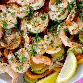 Three skewers of Grilled Garlic Lemon Shrimp along with grilled vegetables with lemon wedges