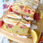 angled side view of zucchini bread on cutting board surrounded by lemons and raspberries