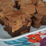 angled side view of brownies on plate with peanut butter cups at side