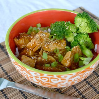 angled view of orange bowl of honey sesame chicken on bamboo place mat
