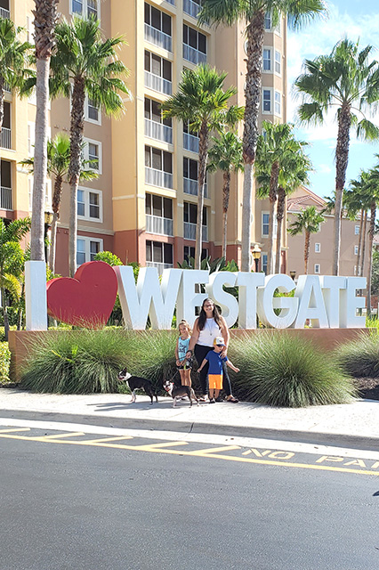Family standing in front of I love Westgate Sign in FL