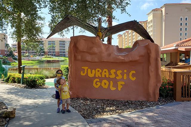 2 kids standing next to Jurassic golf mini golf course at Westgate Resort in Orlando FL