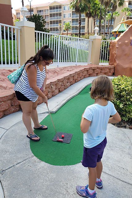 woman playing little girl miniature golf with little girl